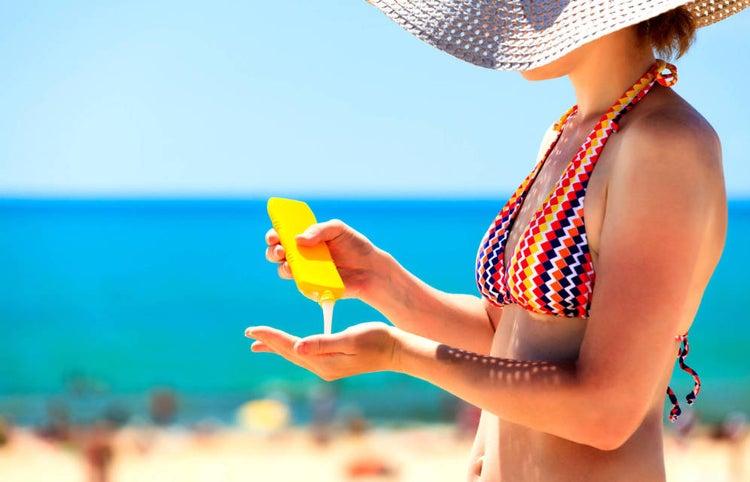 Chica en la playa con protector solar en la mano