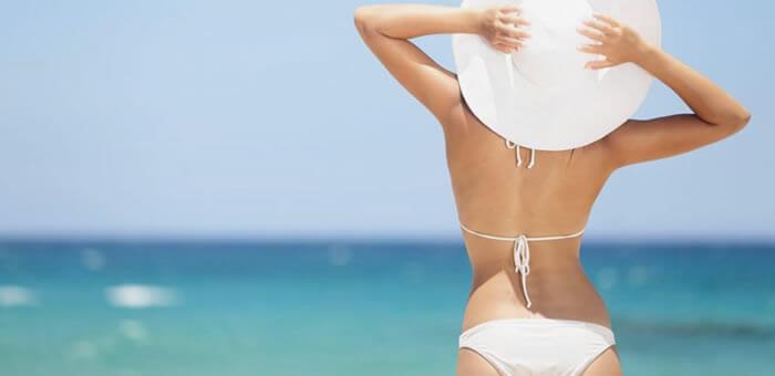 Chica en la playa con bikini blanco