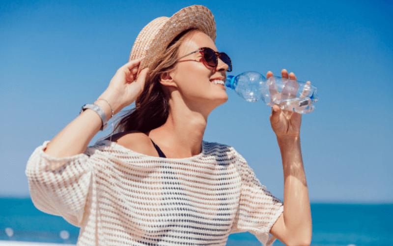 Chica tomando agua en la playa
