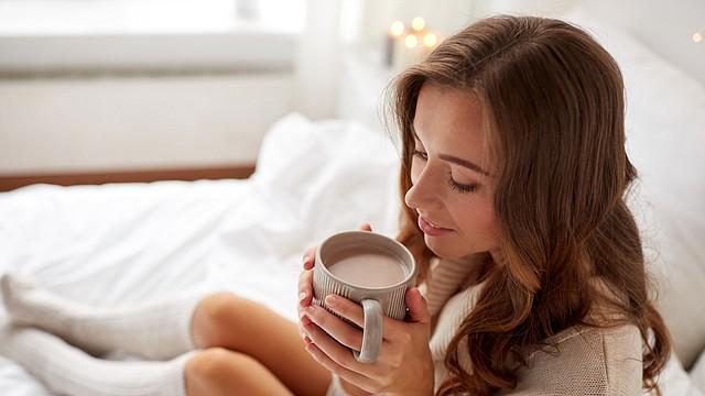 Chica con taza en la cama