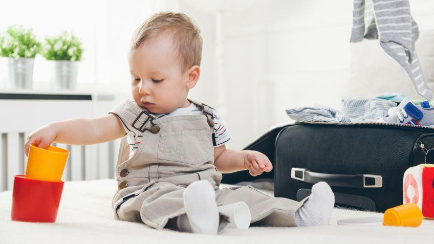 Bebé en la cama con una maleta de viaje a un costado