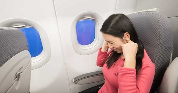 Chica viajando en avión y tapándose los oídos