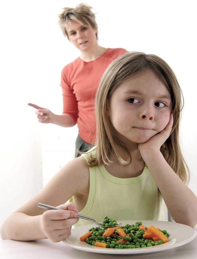 Niña come verduras y suplementos